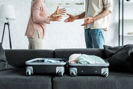 cropped view of man and woman standing and gesturing near suitcase with clothes on sofa