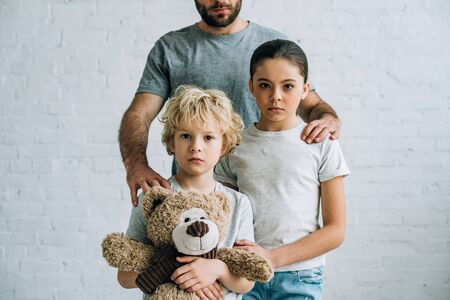 partial view of father and kids with teddy bear at home Stock Photo