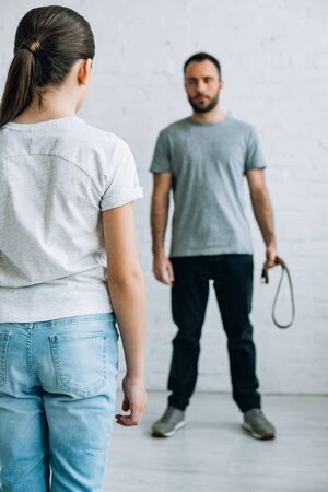 Rückansicht der Tochter, die Vater mit Gürtel in der Hand anschaut