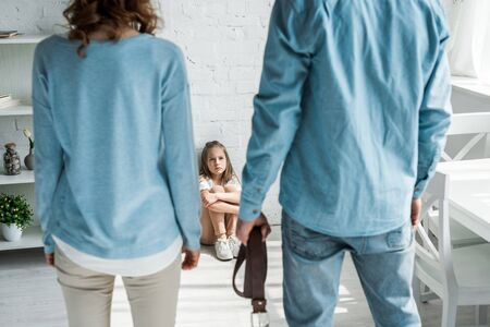 selective focus of scared kid sitting on floor and looking at father with belt standing near mother Stock Photo
