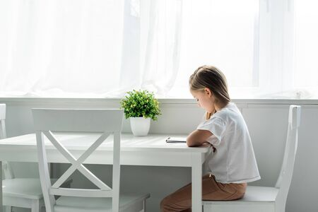 Cute kid sitting and writing in notebook at home