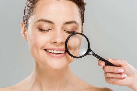 cheerful woman with closed eyes holding magnifying glass near face isolated on grey
