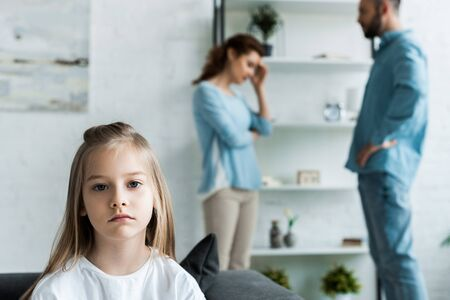 selective focus of upset kid looking at camera near quarreling parents at home
