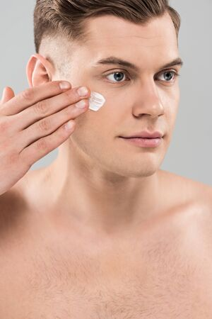 Naked young man applying face cream isolated on grey background
