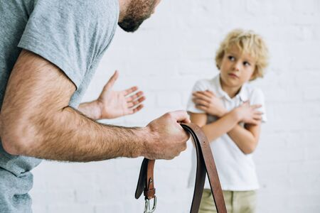 cropped view of father holding belt and scolding son at home
