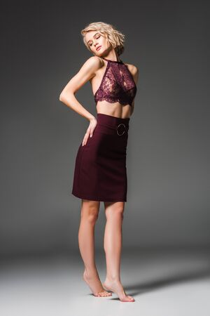 beautiful fashionable girl in burgundy clothes posing on grey Banco de Imagens