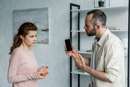 upset man pointing with finger at smartphone with blank screen near woman