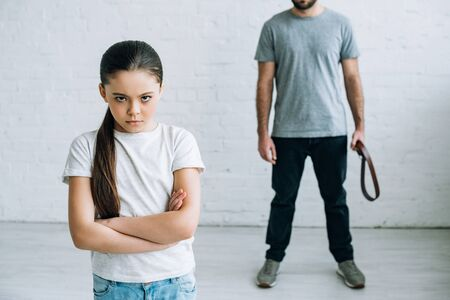 Cropped view of father holding belt and upset daughter at home