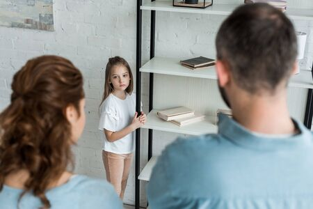 selective focus of upset child looking at parents at home