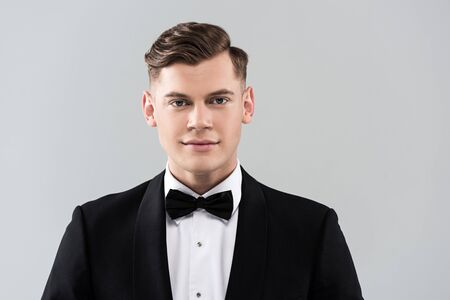 Front view of smiling young man in formal wear with bow tie isolated on grey background 스톡 콘텐츠