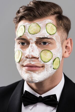 Young man in formal wear with cucumber facial mask isolated on grey background
