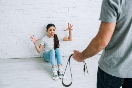 Ausgeschnittene Ansicht von Vater mit Gürtel und verängstigter Tochter, die auf dem Boden sitzt Standard-Bild