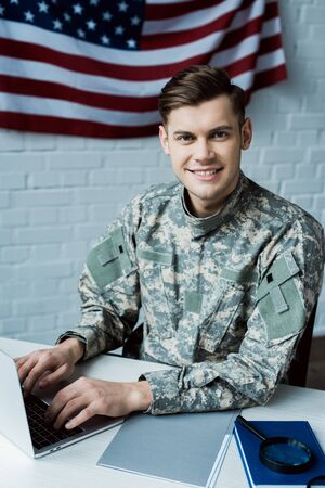 cheerful soldier looking at camera while using laptop in office 版權商用圖片