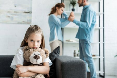 selective focus of sad kid holding teddy bear near quarreling parents at home Stock Photo