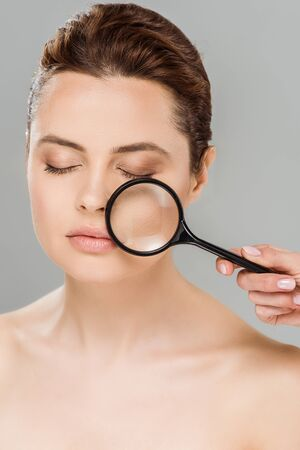 naked woman with closed eyes holding magnifying glass near face isolated on grey