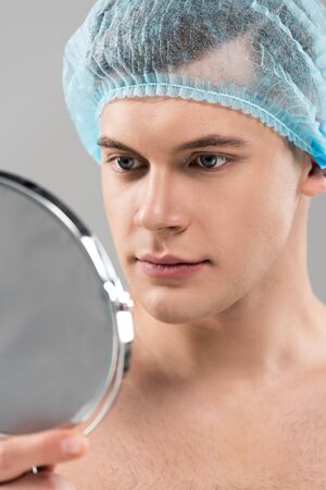 Young man in medical cap looking at looking glass isolated on grey background