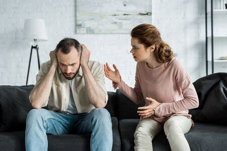upset woman gesturing and looking at man covering ears at home