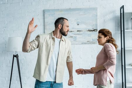 scared woman looking at aggressive husband gesturing at home