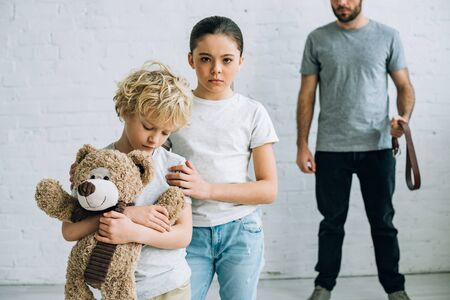 partial view of abusive father with belt and sad kids with teddy bear