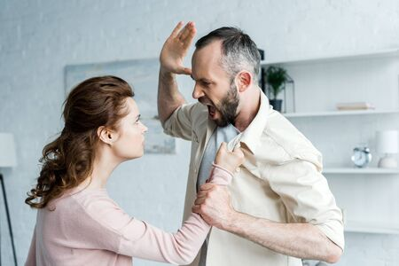 angry man gesturing while threatening and looking at attractive woman