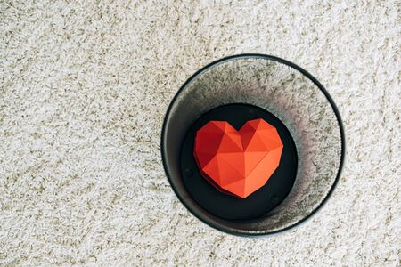 Red heart in black trash can on carpet Stockfoto