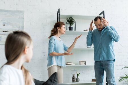 selective focus of offended woman quarreling with husband near kid at home Stock Photo