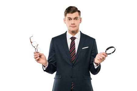 surprised businessman holding glasses and magnifying glass isolated on white