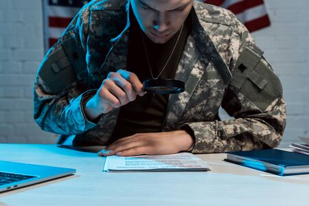 handsome soldier holding magnifying glass while reading document in office Фото со стока
