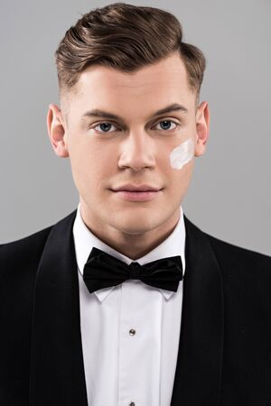 Front view of handsome man in formal wear with cream on face isolated on grey background