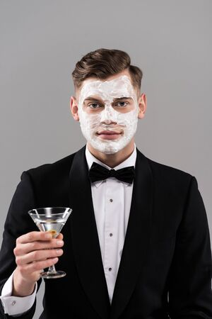 Front view of man in formal wear with cream on face holding glass of cocktail isolated on grey background 스톡 콘텐츠