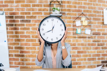 African American casual businesswoman covering face with clock in loft office Stock Photo