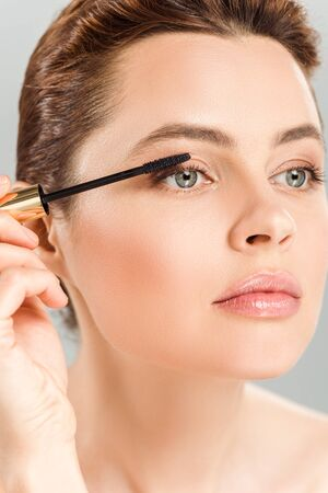 Attractive woman applying mascara isolated on grey background Foto de archivo