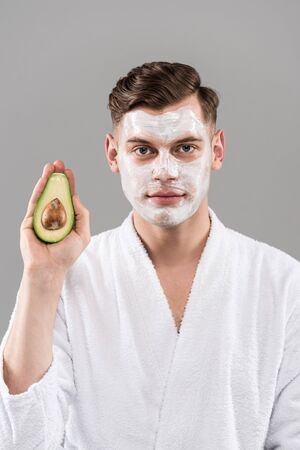 Front view of man in bathrobe with cream on face holding cut avocado isolated on grey background