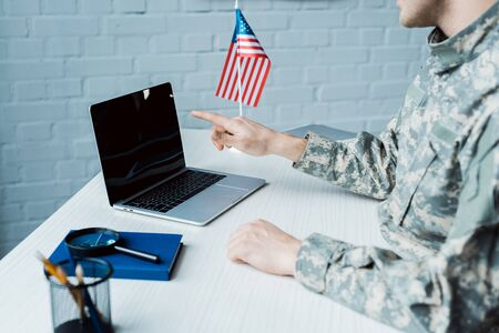 cropped view of military man pointing with finger at laptop with blank screen Фото со стока