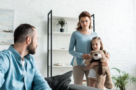 selective focus of kid holding teddy bear near mother while looking at father Stock Photo