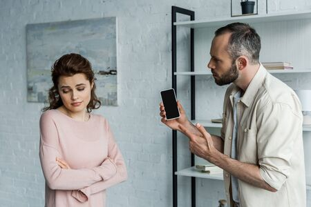 offended man pointing with finger at smartphone with blank screen near woman with crossed arms Stock Photo