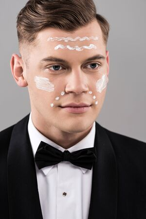 Handsome man in formal wear with cream on face isolated on grey background