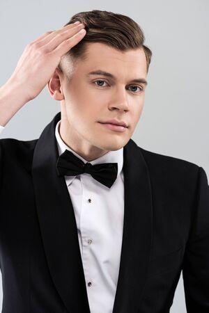 Sonriente joven en ropa formal con pajarita tocando el pelo aislado sobre fondo gris Foto de archivo