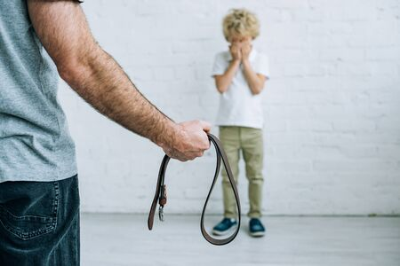 Cropped view of father with belt and crying son at home