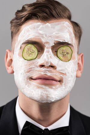 Portrait of young man in formal wear with cucumber facial mask isolated on grey background