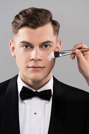 Partial view of cosmetologist applying face cream and man in formal wear isolated on grey background