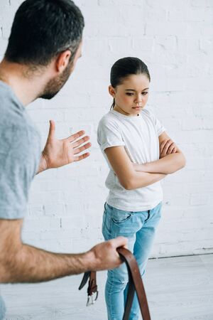 partial view of father holding belt and scolding upset daughter at home Stock Photo