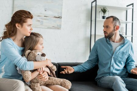 mother hugging daughter with teddy bear and looking at upset husband at home