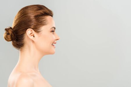 Vue latérale d'une femme joyeuse souriante isolée sur fond gris Banque d'images
