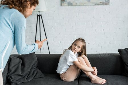Selective focus of kid looking at mother pointing with finger at home