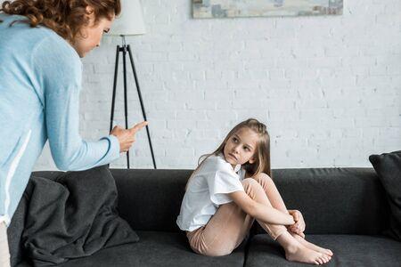 Selektiver Fokus des Kindes, das auf die Mutter schaut, die mit dem Finger zu Hause zeigt Standard-Bild