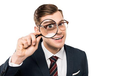 happy businessman holding magnifying glass near eye isolated on white