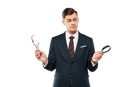 handsome businessman holding glasses and magnifying glass isolated on white Фото со стока