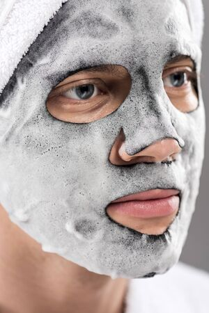 Portrait of man with towel on head and foamy facial mask looking away