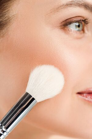 Cropped view woman applying blush on cheek with cosmetic brush